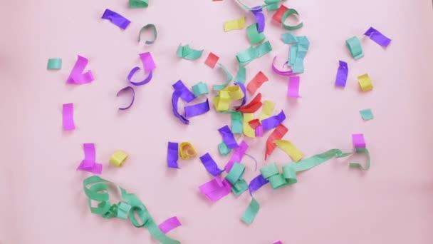 Vícebarevné konfety padající na růžové pozadí