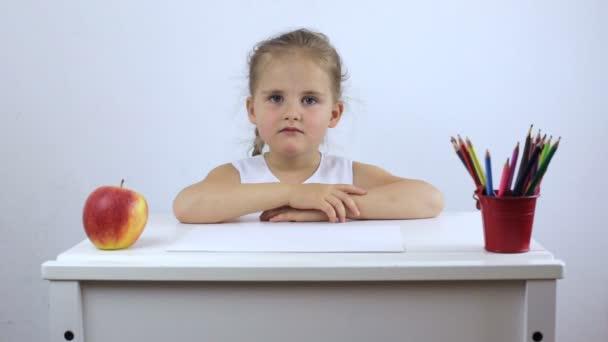 Unavená a frustrovaná malá holčička seděla na školním stole