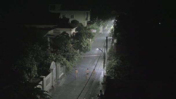 silhouettes of men walking in small street at night while it's raining