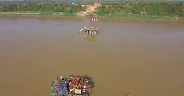 Drohnenschuss aus der Luft: Rückflug über Brückenfundamente und einen Kran im Fluss