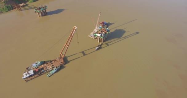 Luftaufnahme von Brückenfundamenten und Lastkähnen auf Kränen im Fluss