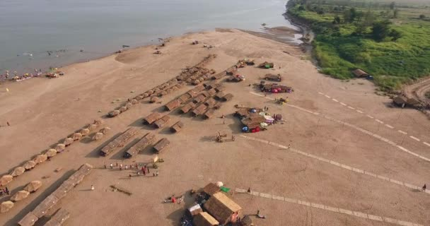 aerial drone shot : fly back over straw huts and wooden bungalows spread over sand beach