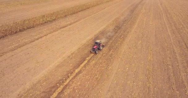 Letecká dron zastřelil: létat přes traktor tahání pluhu Rada plísně v poli. Kukuřičné stonky, které zbyly po sklizené pole.