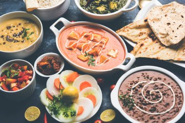 Assorted indian food for lunch or dinner, rice, lentils, paneer, dal makhani, naan, chutney, spices over moody background. selective focus