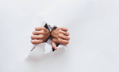 Female hands opening hole in white paper. Breaking obstacles. Escape, protest. Copy space.