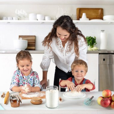 Studio shot of a family in the kitchen at home.  Small children, a girl and a boy, learn to make dough rolls with their mother or nurse.