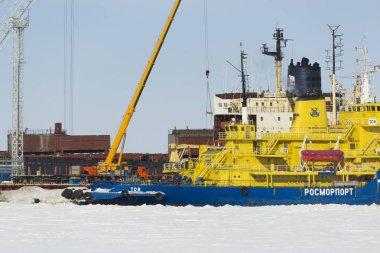 Icebreaker and cranes in the port Sabetta. Russia, Yamal, Kara Sea. Winter sunny