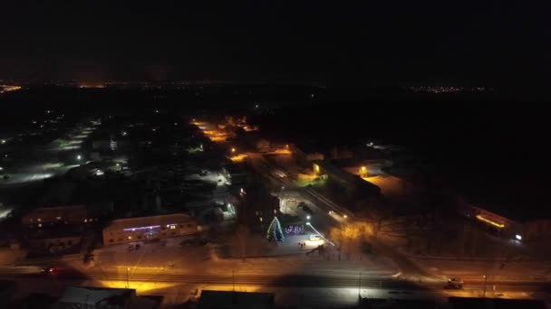 Letecký pohled na noční vesnici v zimě. Po silnicích jezdí auta. Na náměstí je vánoční stromek. Silnice osvětlují pouliční osvětlení