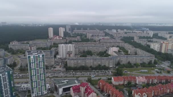 Aerial view of residential city area with old Soviet Russian high-rise houses. Cloudy summer morning. There are new high-rise buildings and old houses. There are many trees and forest around