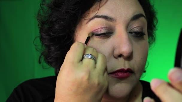 latina in 40s applies eye makeup