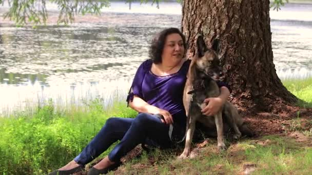 woman and dog sitting under tree