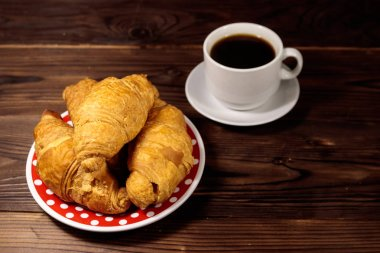 Cup of coffee and plate with fresh croissants on wooden table