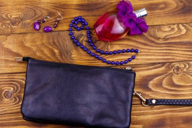Women accessories on wooden background. Clutch bag, bottle of perfume, necklace and earrings on wood table. Beauty and fashion composition. Top view, flat lay