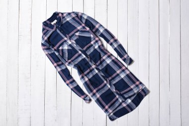 Fashion clothes. Blue checkered long shirt on white wooden floor planks