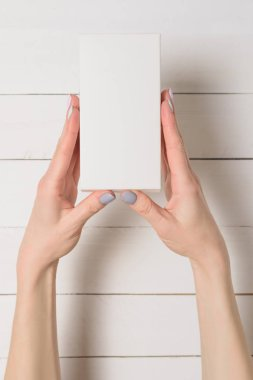 Small rectangular box in female hands. Top view. White table on the background