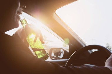 Man drinking beer while driving a car