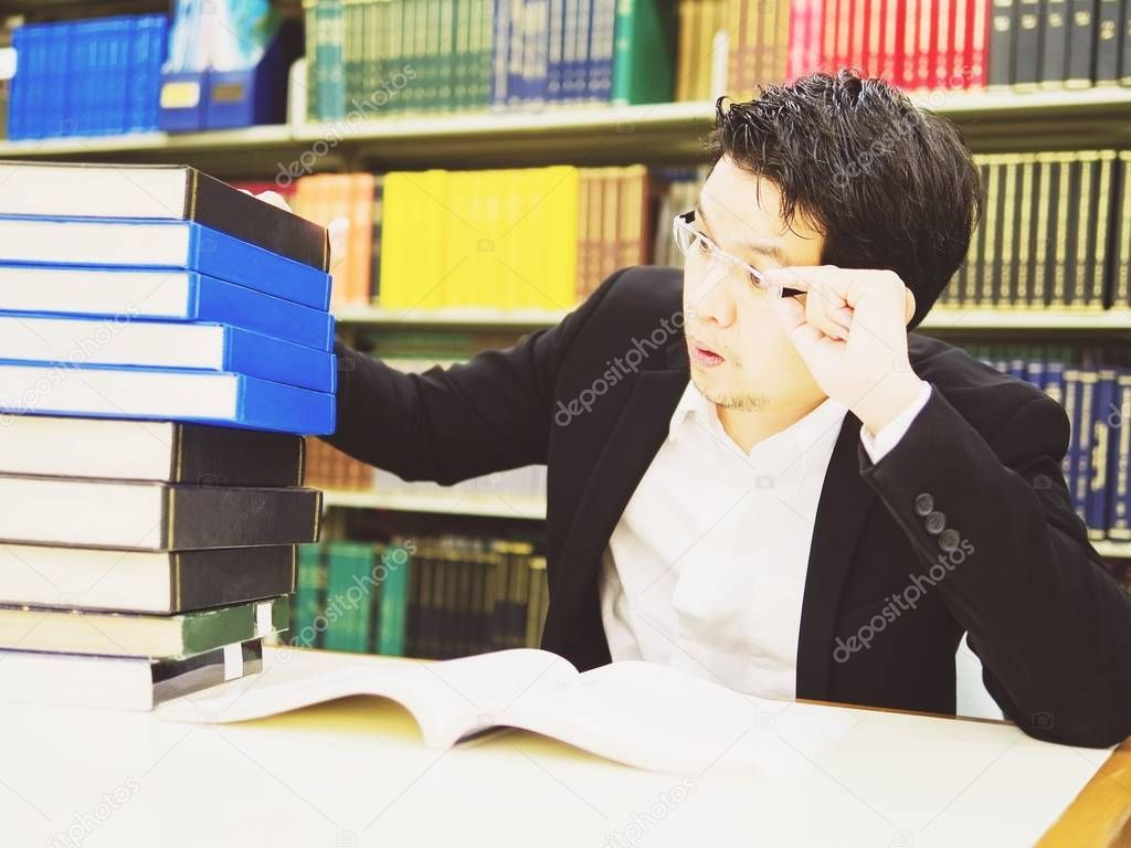 Business man looking at a pile of book in library panicly