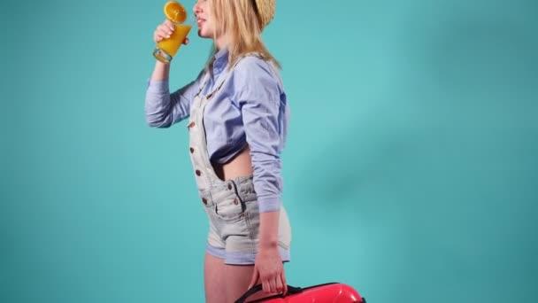Hezká dívka drží červený kufr a pije pomerančovou šťávu. Dívka se létání na cestu