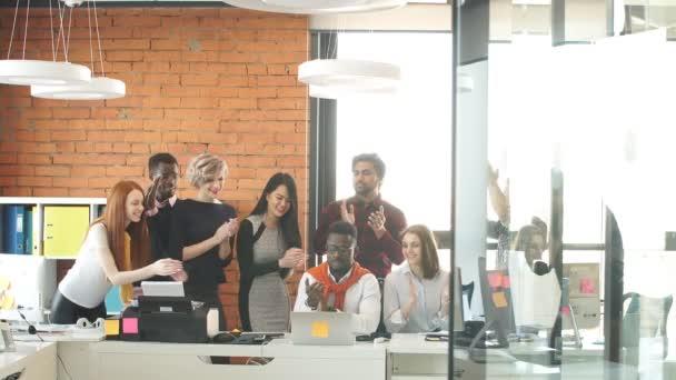 Mladí programátoři jsou shromážděni a s příjemnou konverzaci na pracovišti v místnosti s interiéru podkroví.
