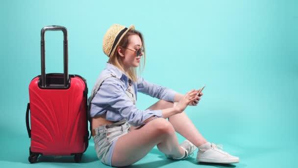 GRL s červenými kufr na modrém pozadí pomocí smartphonu.