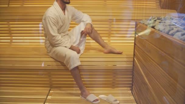 Mladý pohledný muž v bílém rouchu se zahřívá v sauně.