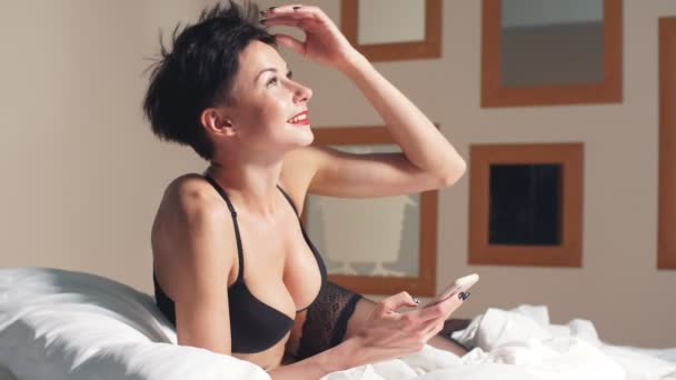Luxusní brunetka model s přírodními velkými bubs v podprsenka ležící na posteli při pohledu na smartphone.