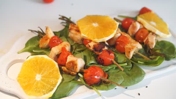 Chicken kebabs served with tomato cherry and greenery