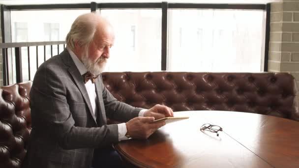 Portrait of a mature businessman with digital tablet.