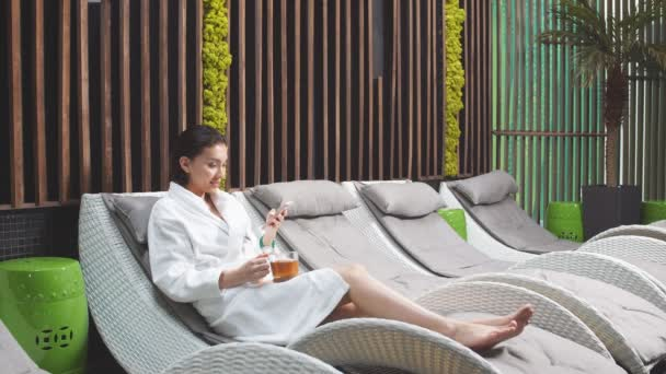 Attractive Woman Drinking Tea and Using Smart Phone in Spa Center.