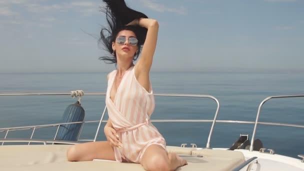 Portrait of brunette female posing over sea marine background on sailing boat