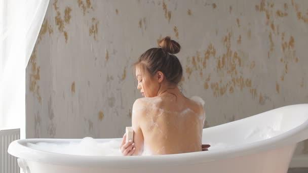 žena sama omývání mýdlem na koupel s pěnou.