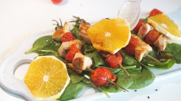 Kuřecí kebab podávaná s rajčaty třešeň a zeleň na bílé prkénko na sporák, zblízka