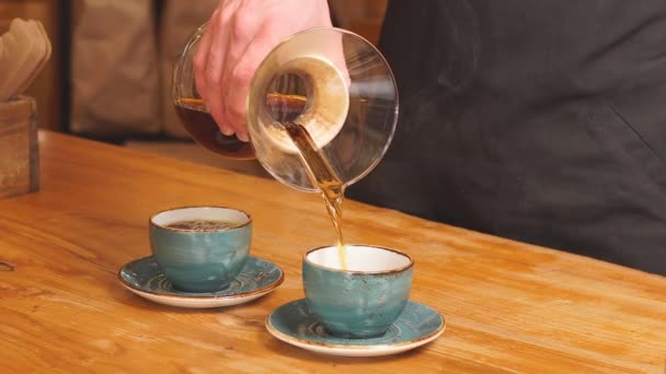 Coffeemaker is pouring beverage into the cups