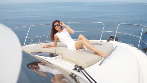 Beautiful brunette woman in white dress posing on boat