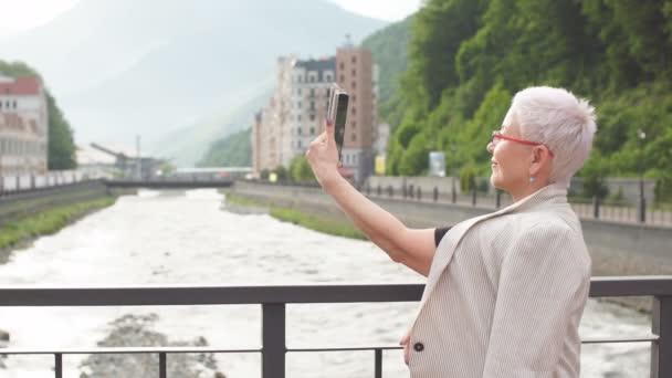 Krásná starší žena dorazila v cizím městě a pořizování fotografií zde