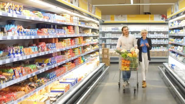 male and female shoppers push cart with grocery products in supermarket aisle