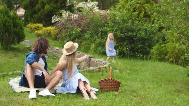 happy Family picnicking outdoors with their cute daughter, blue clothes, woman in hat