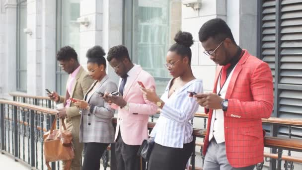 Attractive employees are resting with cell phones after meeting near the office building.