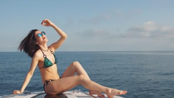 Junges Mädchen im Bikini und Sonnenbrille posiert an einem sonnigen Sommertag auf einer Jacht