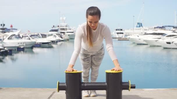 Sportive žena trénink venku dělá crossfit cvičení u moře mola