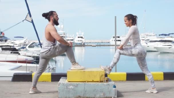 Krásný mladý pár dělá protahovací cvičení v oceánu pier