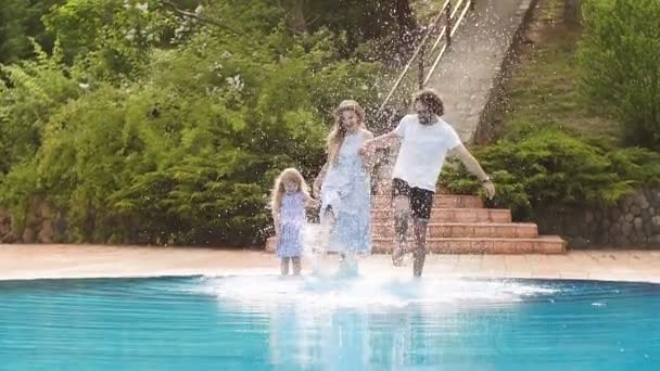 Family vacation in summer. Parents with kid having fun near swimming pool
