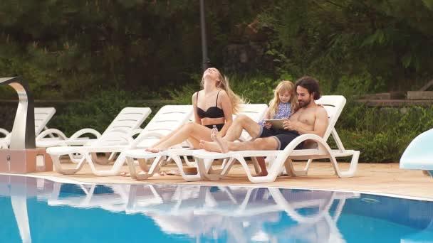 dítě a rodiče relaxační na lehátko u bazénu v resort. Móda dívky, pár, rodinný Resort