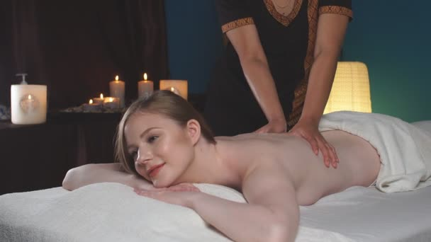 Mladá, krásná žena v lázeňském salonu ležící na kočáře a čekající na masáž.