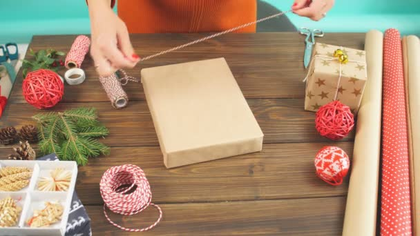 Female hands wrapping Christmas gift in craft ecological paper on dark wooden backround