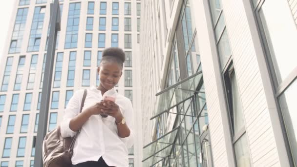 African american woman with backpack walking outdoor and talking on mobile phone