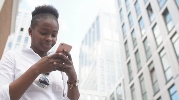 Afrikanerin benutzt Smartphone, während sie auf weißen Treppen im Freien sitzt.