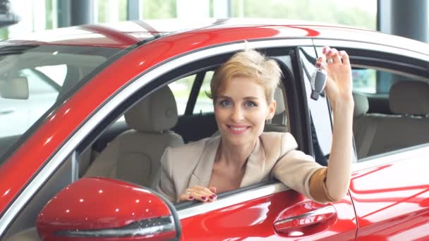 Overjoyed driver woman smiling and showing new key while sitting in car showroom