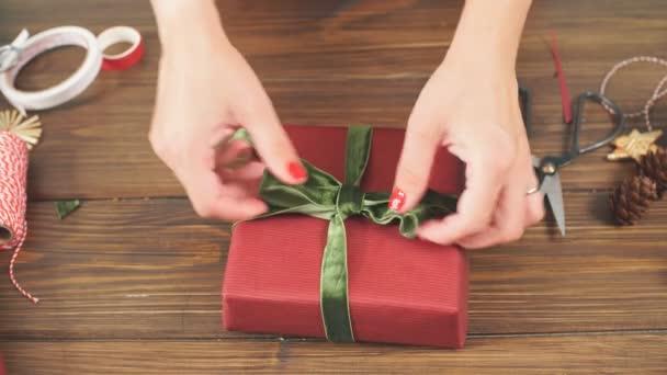 Női kezek díszítő vörös díszdobozok, a karácsonyi ünnep. Kezek közelről.