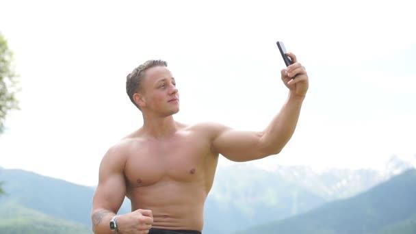 Muž držící chytrý telefon a brát selfie venku přes hory přírody.